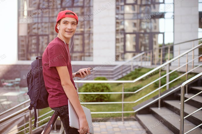 Smiling teenager holds cell phone and laptop, in the city.