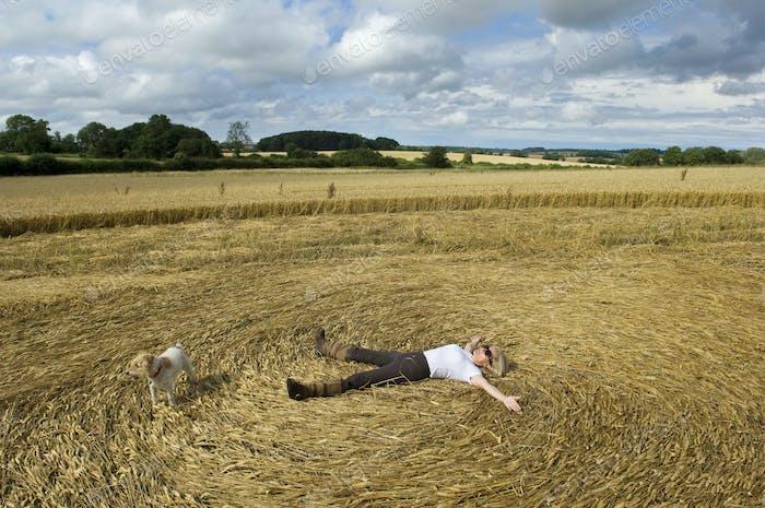 Ein Bauer liegend auf dem Rücken im Stoppeln eines frisch geschnittenen Erntefeldes