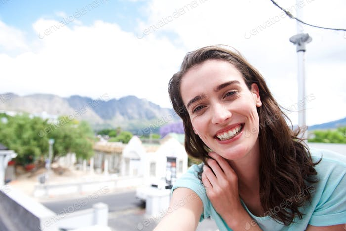 Woman taking selfie portrait outdoors