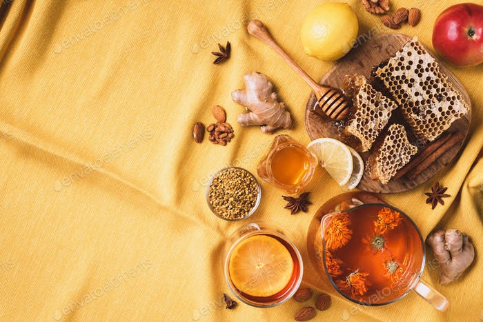 Ingredients for healthy hot drink. Lemon, calendula, ginger, mint, honey, apple and spices over