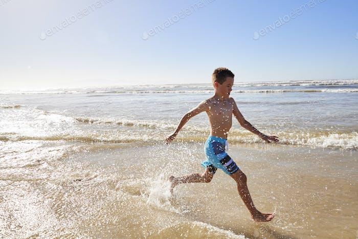 Boy On Summer Vacation Running Through Waves