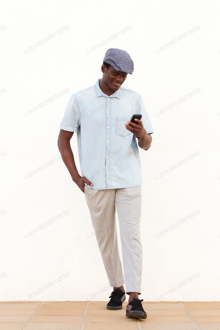 Full length handsome african man reading text message on his mobile phone