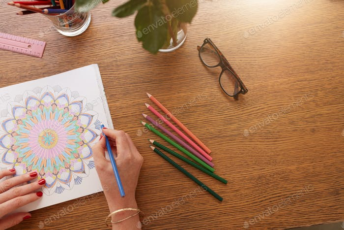 Female hands drawing in adult colouring book