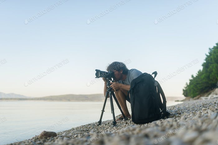Male photographer taking photos on a pebble beach