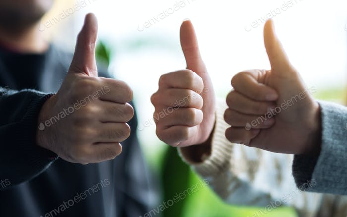 A group of people making thumb up hands sign