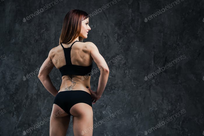 Dark contrast photo of back side of young beautiful fitness woman with beads of sweat which training