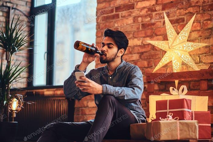Un hombre bebe cerveza.