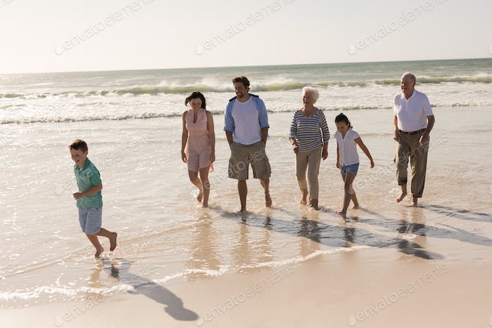 Front view of happy multi-generation family walking and having fun on beach in the sunshine