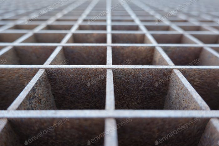 Closeup image of a metal pattern with rust and a shallow depth of field