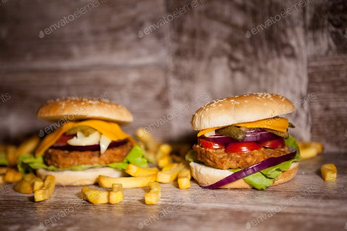 Tasty burgers on wooden plate
