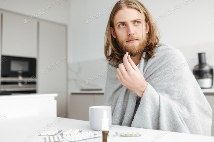 Ill man sitting with mug and dreamily looking aside while holding pill in hand in kitchen at home