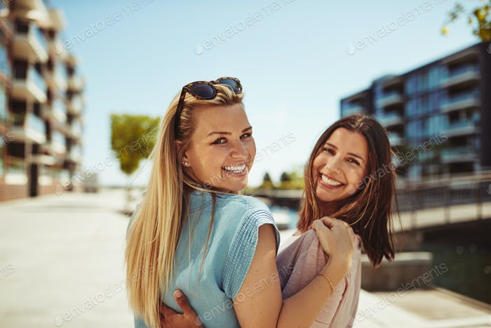 Two young female friends walking in the city laughing together