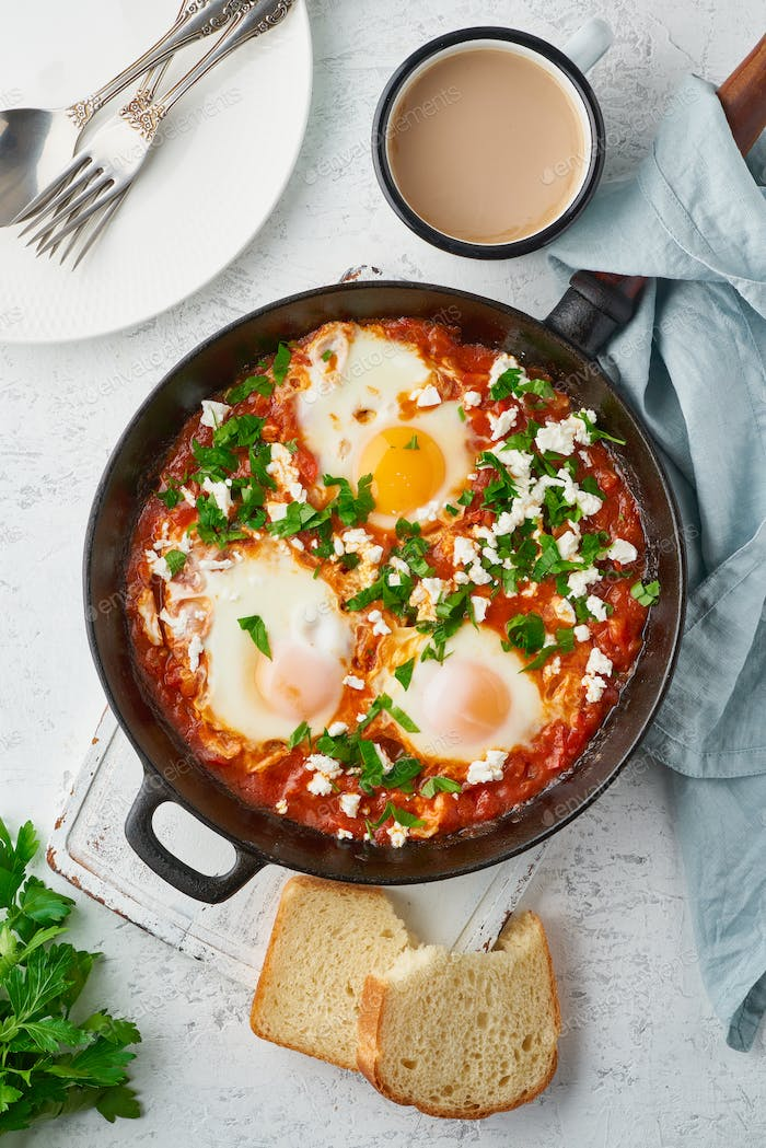 Shakshouka, eggs poached in sauce of tomatoes, olive oil. Mediterranean cuisine.