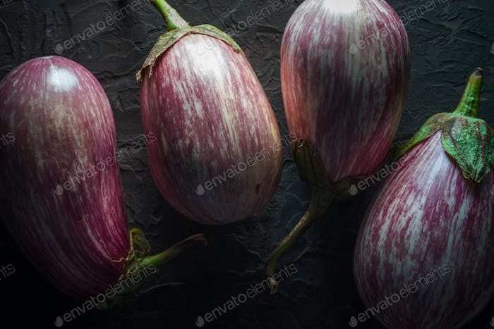 Aubergines with branches in stripes on a dark gray stone close-up