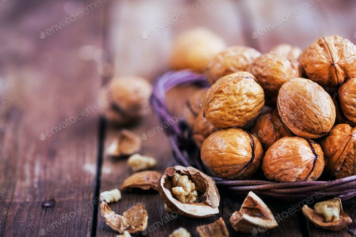 Nueces enteras en cesta sobre mesa rústica de De madera vieja