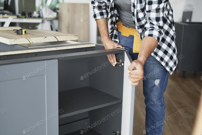 Carpenter installing furniture hinges