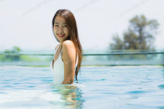 Beautiful young asian woman happy and smile in swimming pool for