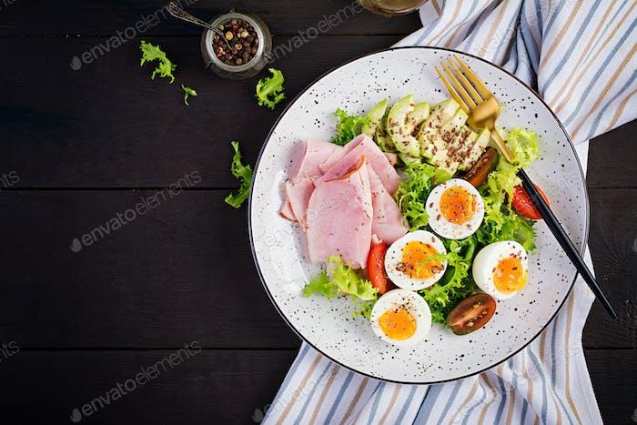 Ketogene/Paleo-Diät. Gekochte Eier, Schinken, Avocado und frischer Salat.