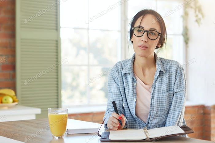 Home interior. Attractive woman wears casual clothes, writes plan in diary, has pensive expression.