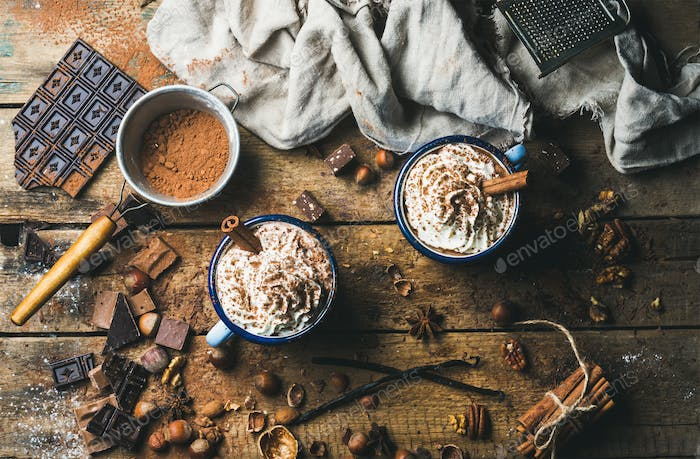 Hot chocolate with whipped cream, nuts and cinnamon in mugs