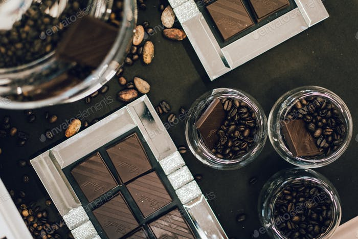 Aerial shot of dark chocolate and coffee beans in glass