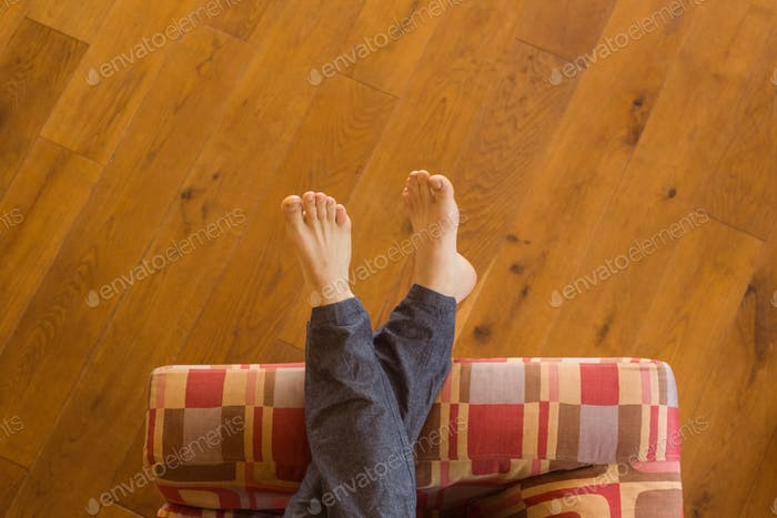 Mans legs on the couch at home in the living room