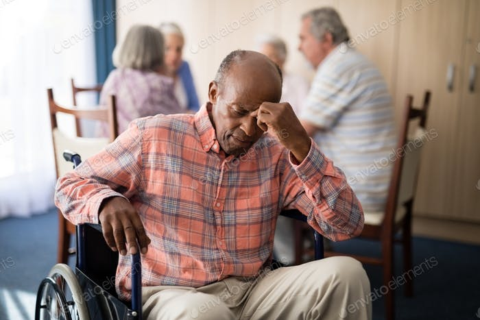 Depressed disabled senior man sitting on wheelchair
