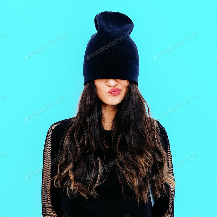 Emotional brunette in black beanie cap. Stylish urban look