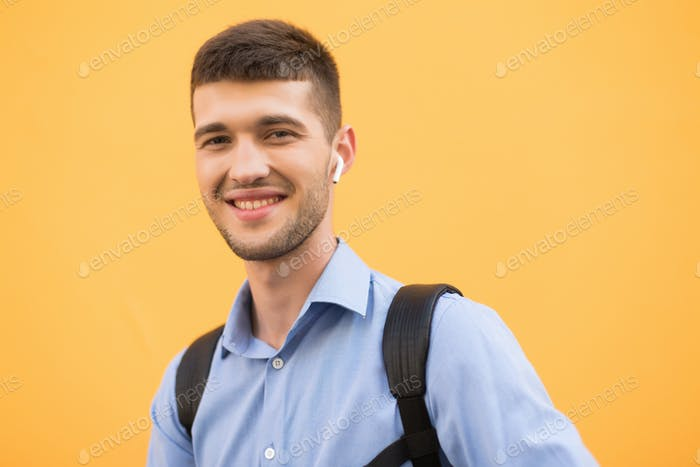 Young cheerful man in blue shirt and backpack with wireless earp