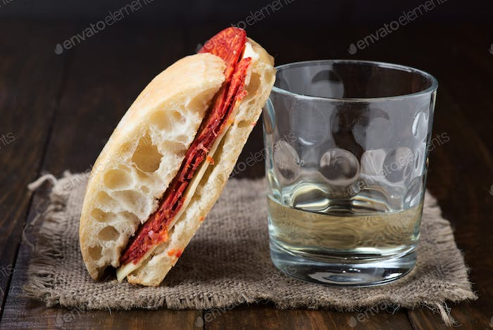 spanish home sandwich of chorizo and cheese, on classic wooden board