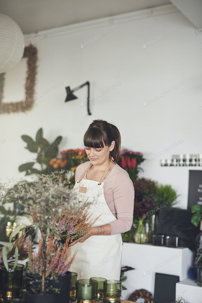 Smiling female florist standing in her shop arranging flowers