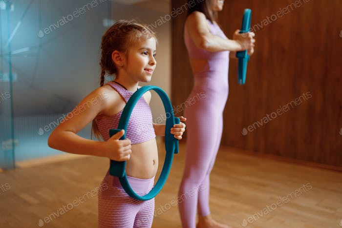 Mother and daughter in gym, pilates with rings