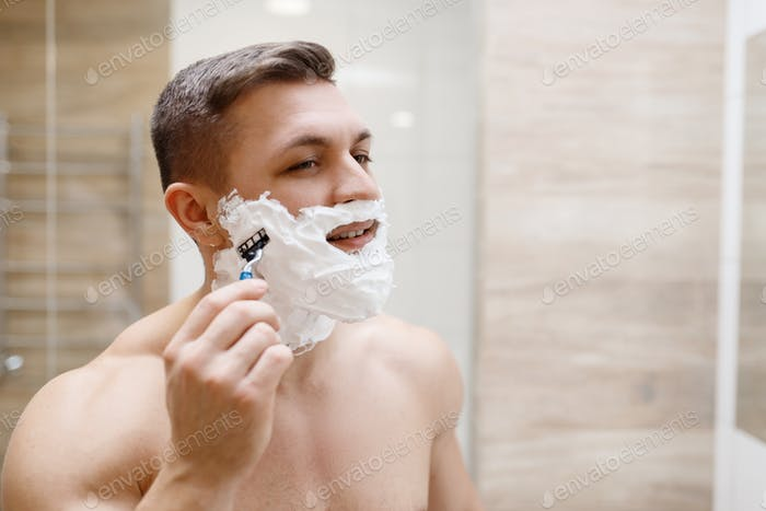 Man shaves his beard with razor in bathroom