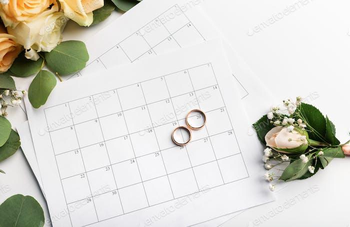 Planning wedding date in calendar, gold rings