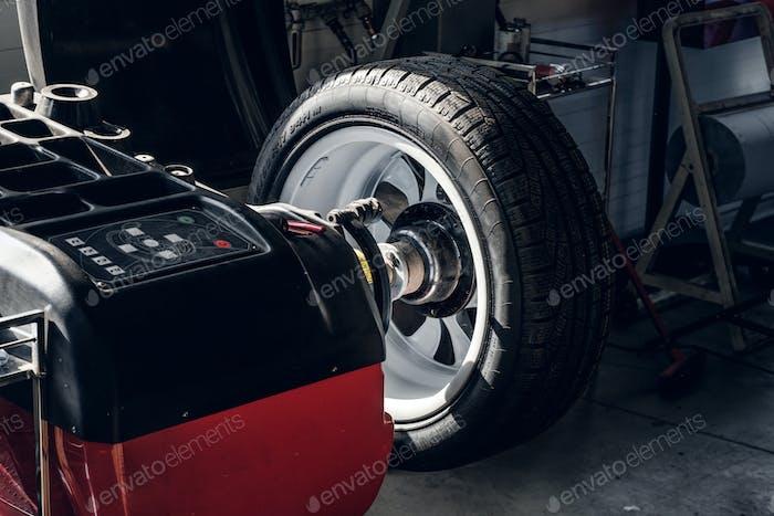 Parts of broken red car in workshop
