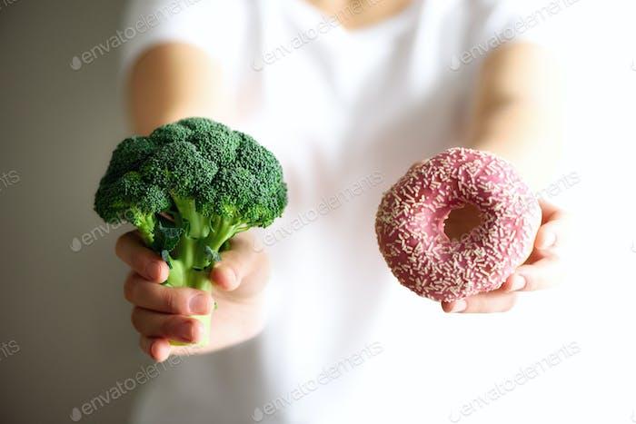 Mujer joven en camiseta blanca elegir entre brócoli o comida chatarra, donut. Desintoxicación limpia y saludable  .