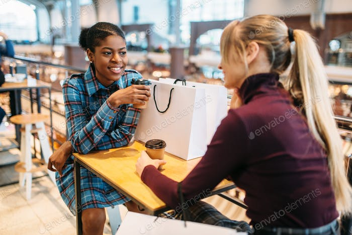 Two girlfriends in food-court after shopping