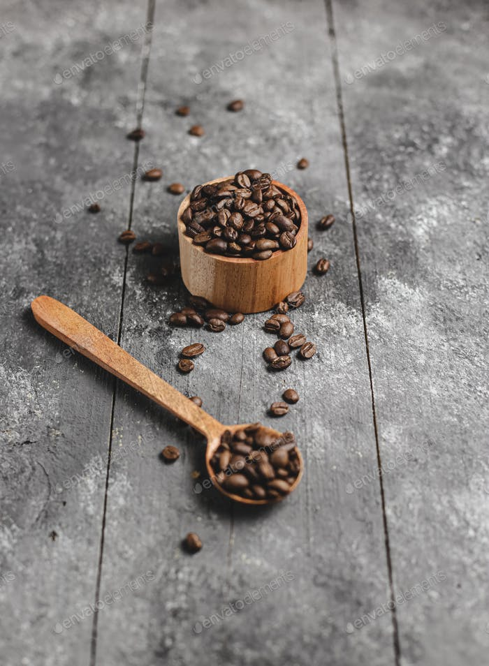 coffee beans in wood saucer and wood spoon with grunge black background