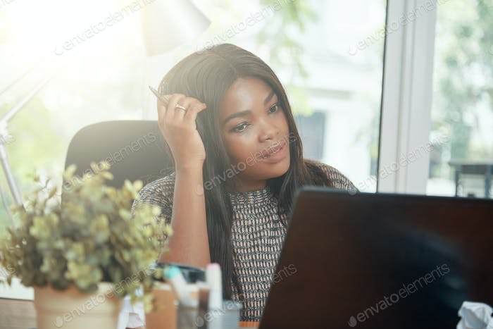 Pensive adult black businesswoman in sunny office