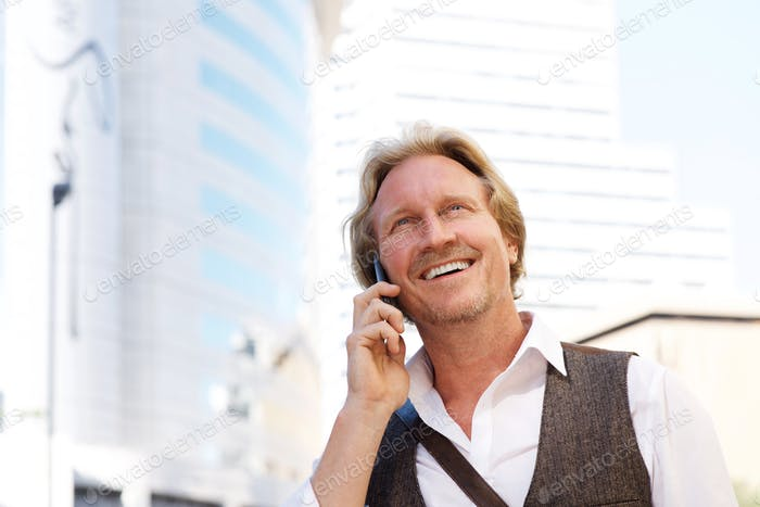 handsome middle aged man talking on mobile phone in city