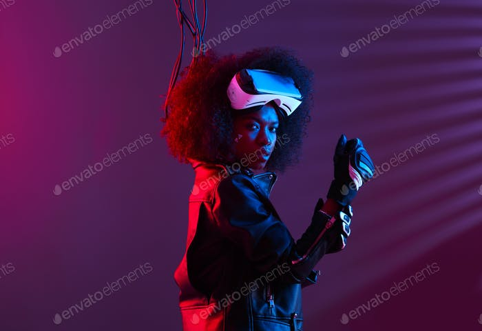 Curly dark haired girl dressed in a black leather jacket and gloves is wearing the virtual reality