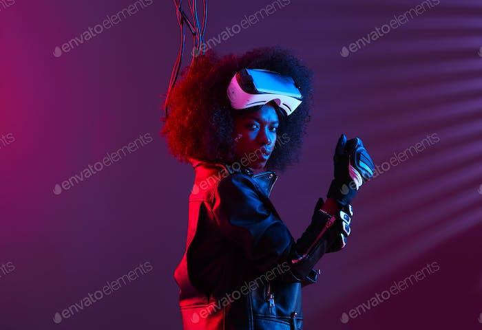 Curly dunkelhaarige Mädchen gekleidet in einer schwarzen Lederjacke und Handschuhe trägt die virtuelle Realität