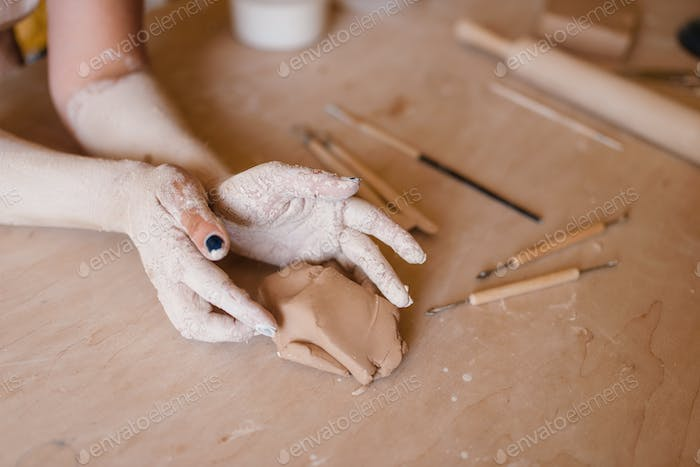 Female potter hands covered with dried clay