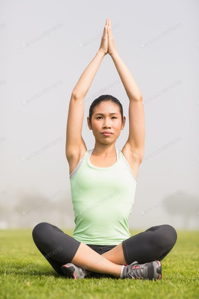 Focused sporty woman doing yoga in parkland