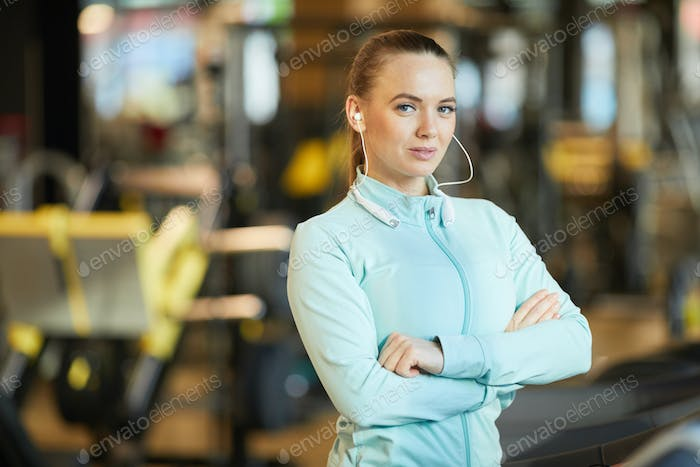 Waist Up Portrait of Young Woman Wearing Earphones in Gym