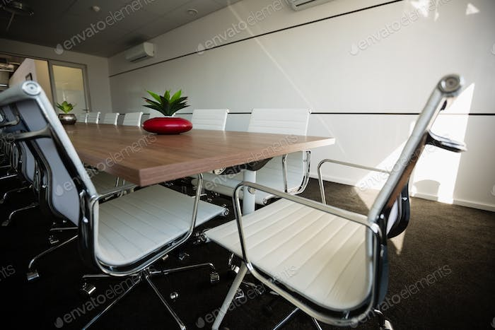 Empty chairs by conference table at office