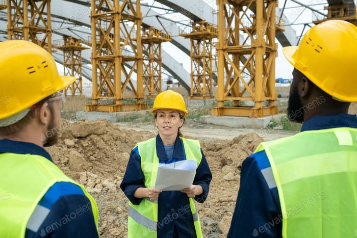 Female engineer in workear talking to her male colleagues