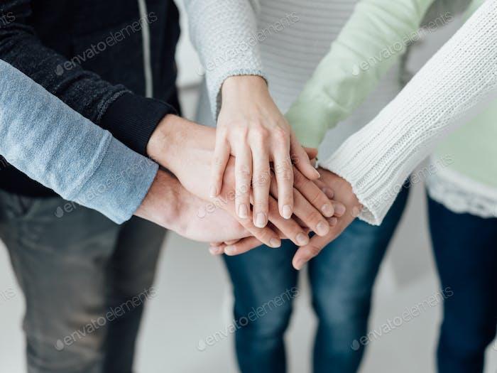 Junge Menschen, die Hände stapeln