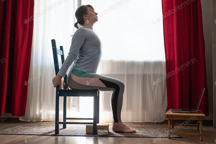 Woman doing exercises at home using chair. Urdhva hastasana asana.