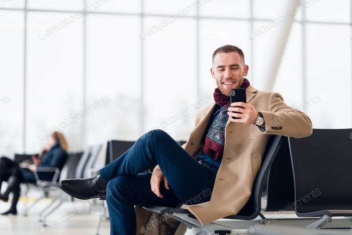 Attractive young adult man in stylish scarf and coat sitting inside airport terminal waiting area